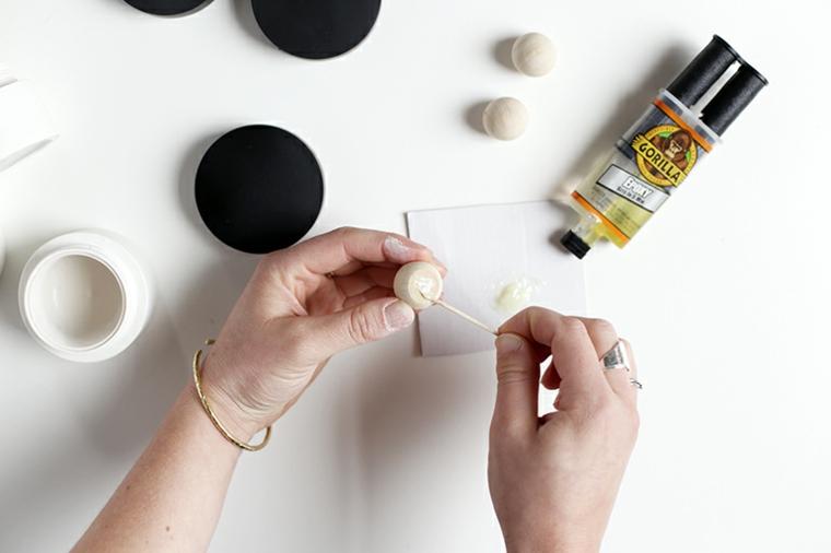 Riciclare oggetti da buttare, donna che incolla una maniglia di legno sul tappo