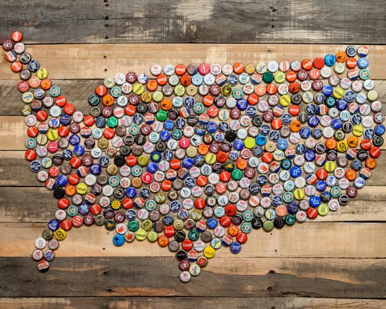 idee-riciclo-creativo-cartina-geografica-tappi-bottiglie-colorati-incollati-asse-legno