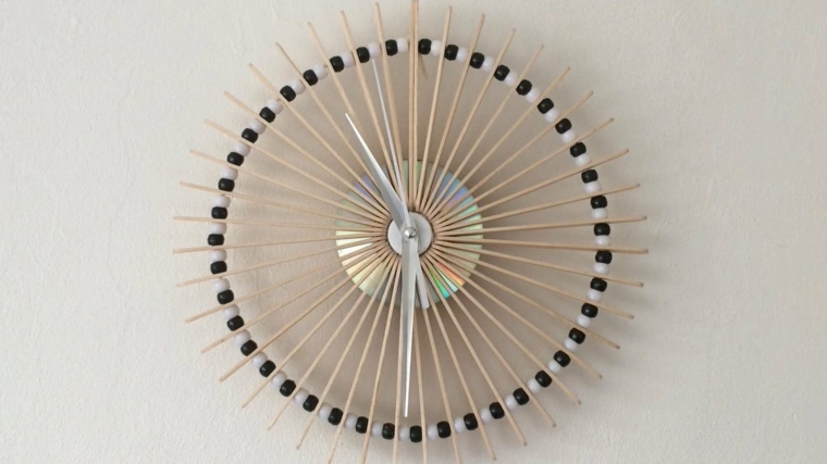 idee-riciclo-orologio-stilizzato-forma-rotonda-bastoncini-legno-palline-bianche-nere