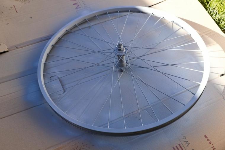 Ruota di una bicicletta dipinta di colore grigio, riciclare oggetti da buttare