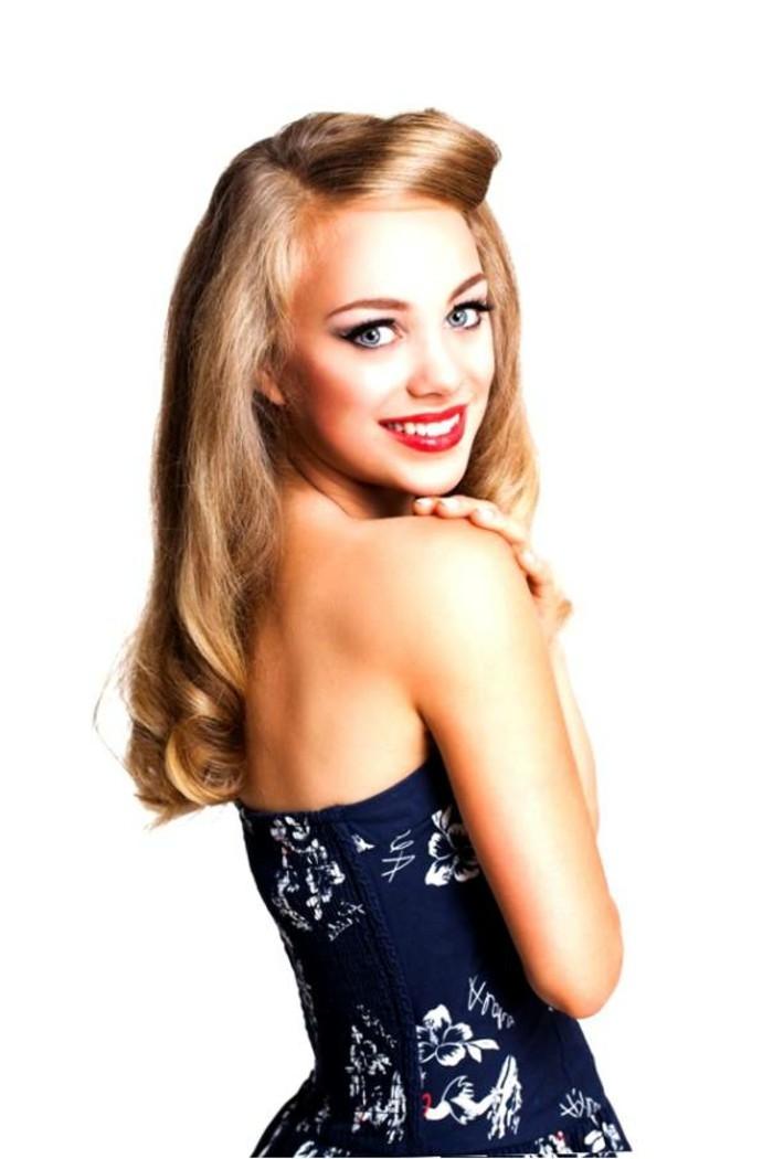 look-anni-50-capelli-biondi-donna-giovane-labbra-rosse-rossetto-vestito-blu-schiena-scoperta
