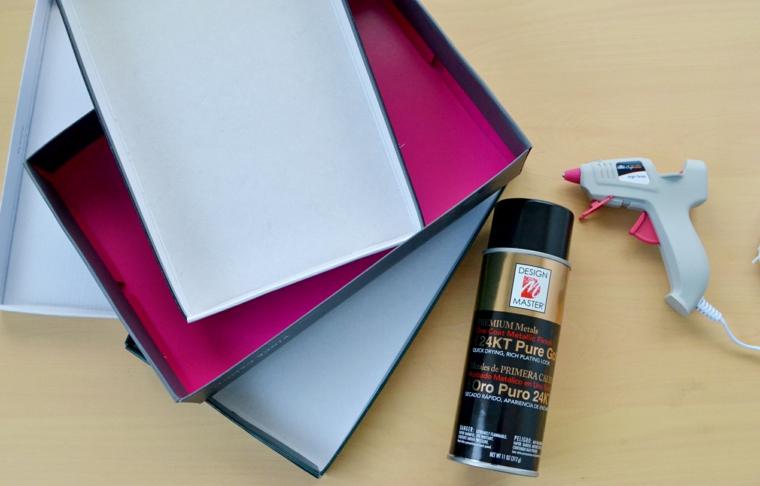 Materiali per un organizer per i trucchi, scatola di cartone accanto ad una pistola per colla a caldo e bottiglia con vernice spray