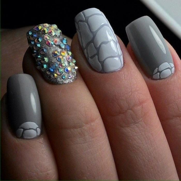 nail-art-particolari-anulare-ricoperte-brillantini-colorati-smalto-grigio-chiaro-grigio-scuro-disegni-effetto-pietra