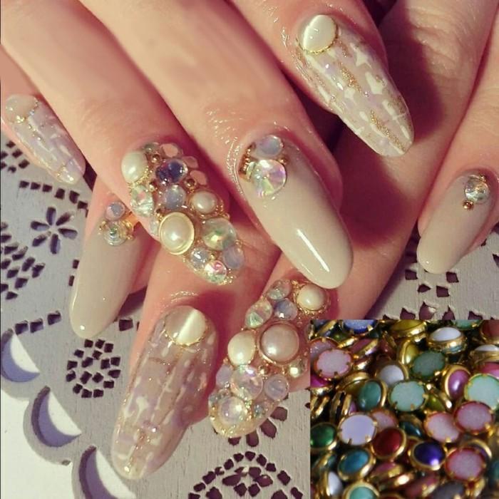 nail-art-particolari-brillantini-pietre-varie-misure-contorno-dorato-base-colore-neutro