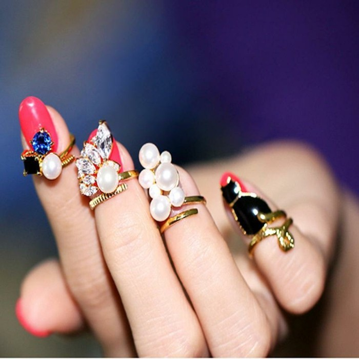 nail-art-particolari-unghie-smalto-rosso-design-perle-pietre-brillantini-anelli-dorati-decorazione