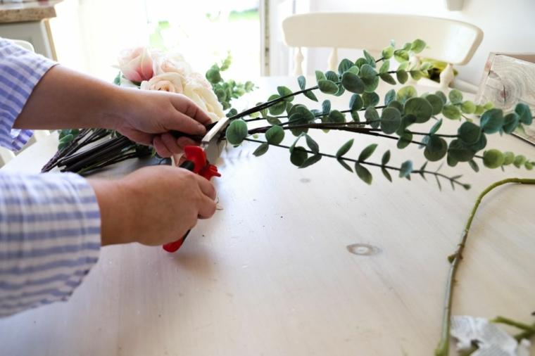 Lavoretti con materiale da riciclare, donna che taglia con le pinza dei rami con foglie