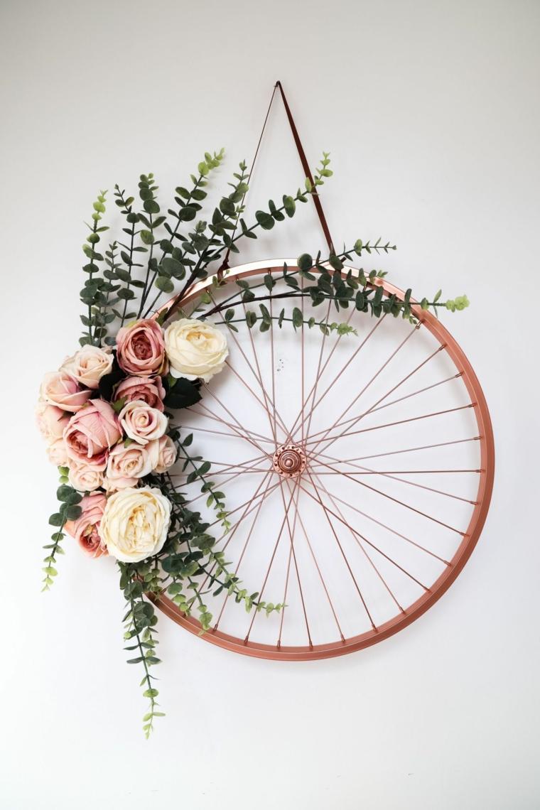 Riciclo creativo, ruota della bicicletta dipinta e decorata con fiori appesa alla parete