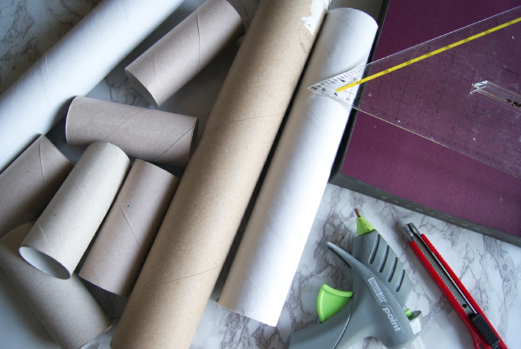 Materiali su un tavolo di marmo, rotoli di carta igienica e pistola per colla a caldo