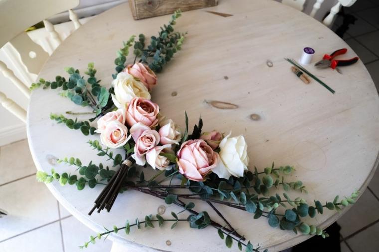 Lavoretti creativi da fare a casa, rametti e fiori su un tavolo rotondo di legno