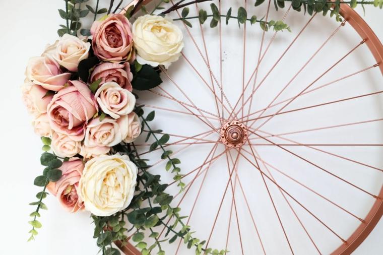 Ruota di una bicicletta con fiori appesa alla parete, lavoretti con materiale da riciclare