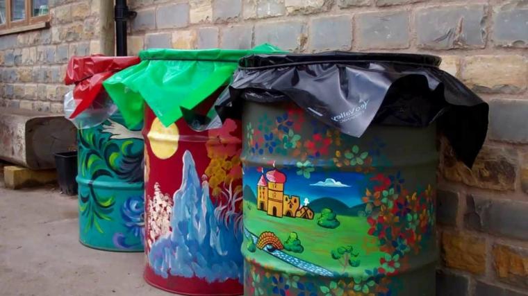 riutilizzo-creativo-bidoni-metallo-dipinti-colori-vicaci-raccolta-differenziata-pattumiera-esterno