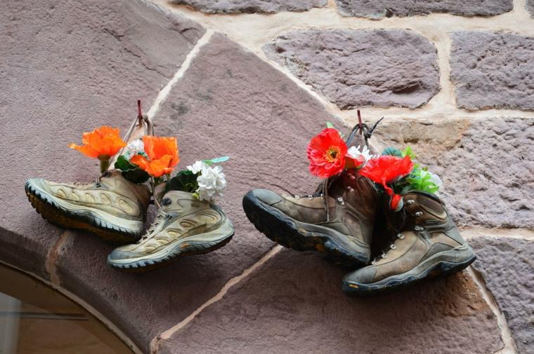 riutilizzo-creativo-vecchi-scarponcini-vasi-fiori-rossi-gialli-appendere-appoggiare-davanzale