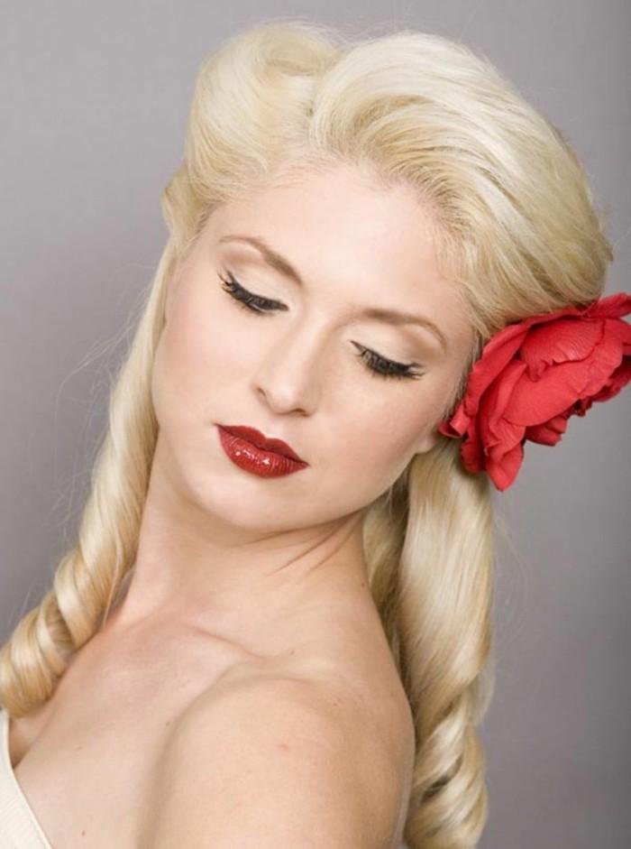 rockabilly-pin-up-acconciatura-donna-capelli-biondi-fiore-finto-rossetto-rosso-sguardo-serio