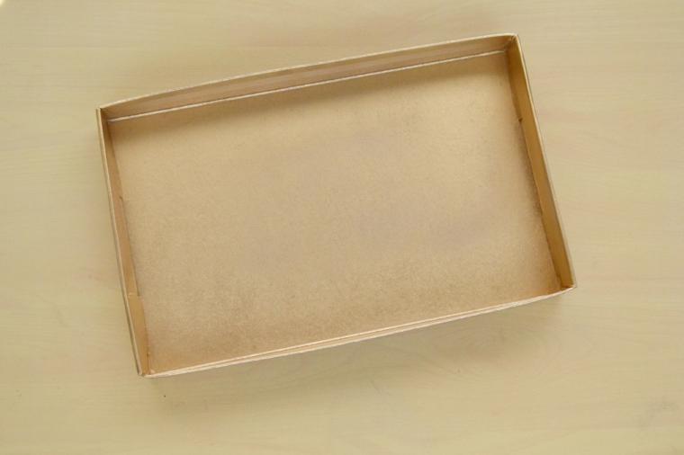 Dipingere una scatola di cartone con vernice in spray colore oro, tutorial per fare un organizer per trucchi