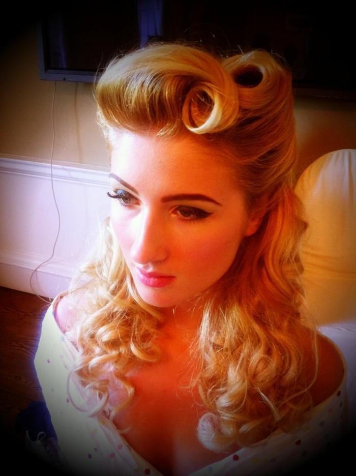 stile-anni-50-idee-capelli-acconciatura-donna-bionda-boccoli-pin-up-forcine-vestito-bianco