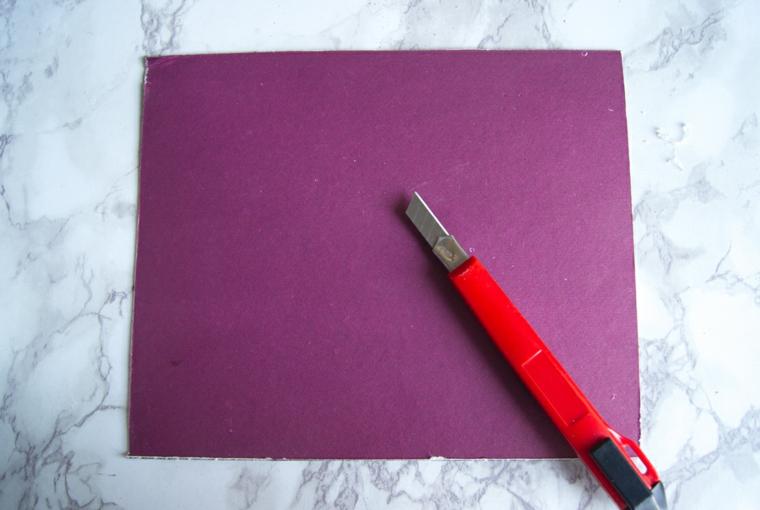 Taglierino su un foglio di carta di colore viola, materiali per fare un organizer da scrivania