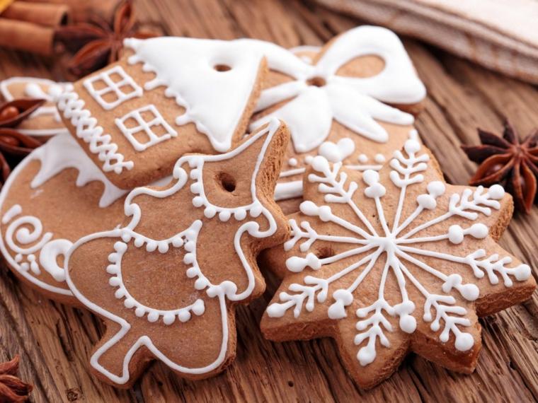 Dolci di Natale e biscotti al cacao decorati con della glassa reale di colore bianco e buchini per essere appesi