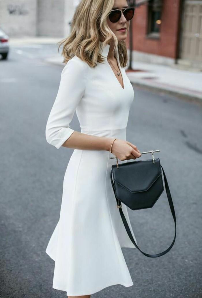 Vestirsi-alla-moda-donna-vestito-elegante-colore-bianco-scollatura-V-borsetta-nera-tracolla-manico-metallo-occhiali-da-sole