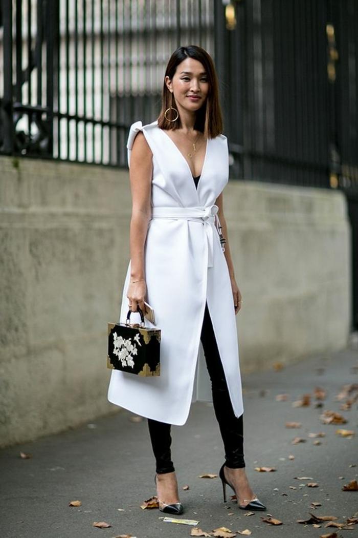 abbigliamento-casual-chic-donna-trench-senza-maniche-bianco-pantaloni-neri-tacchi-alti-borsa-particolare-accessori-abbinare