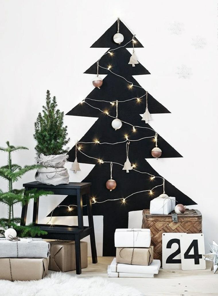 Decorare l'albero di Natale alternativo con una catena di luce e campane, pacchi regalo sotto e caldendario