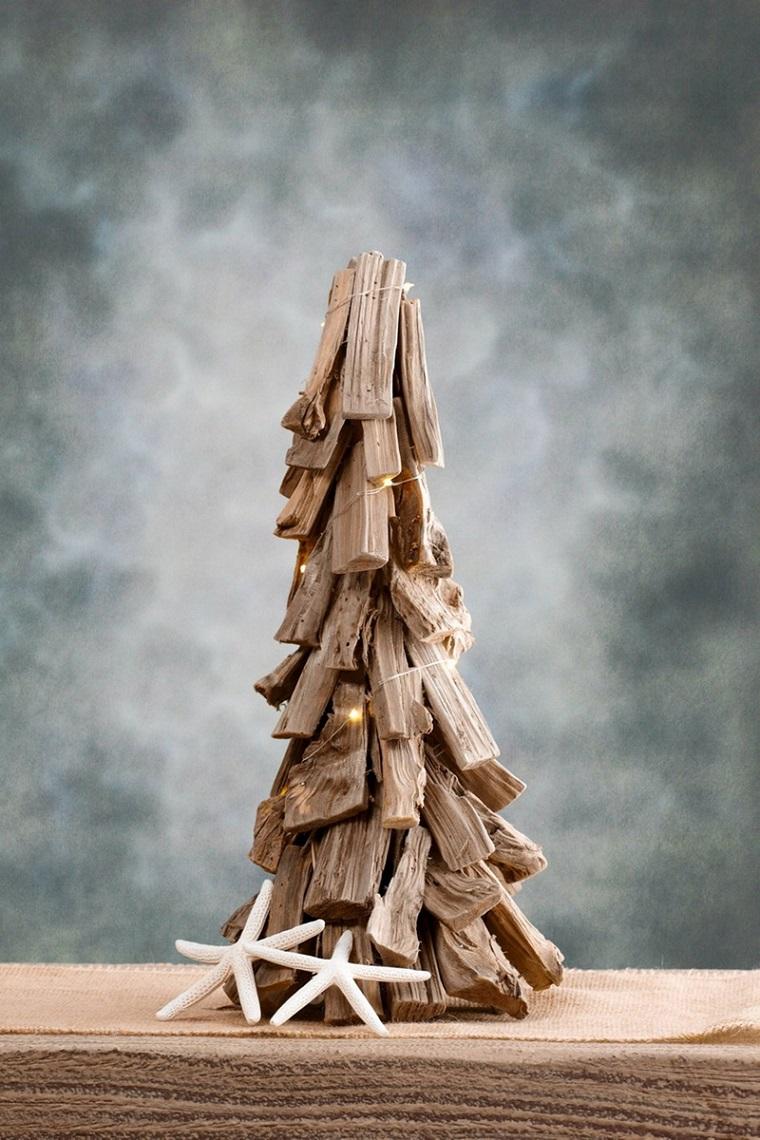 Riciclo creativo di vari legnetti assemblati come un albero di Natale con catene di luci e stelle marine
