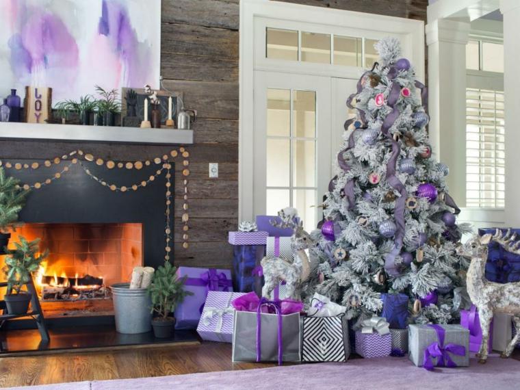 Un albero di Natale tradizionale di colore bianco con addobbi di colore viola con palline e ghirlande