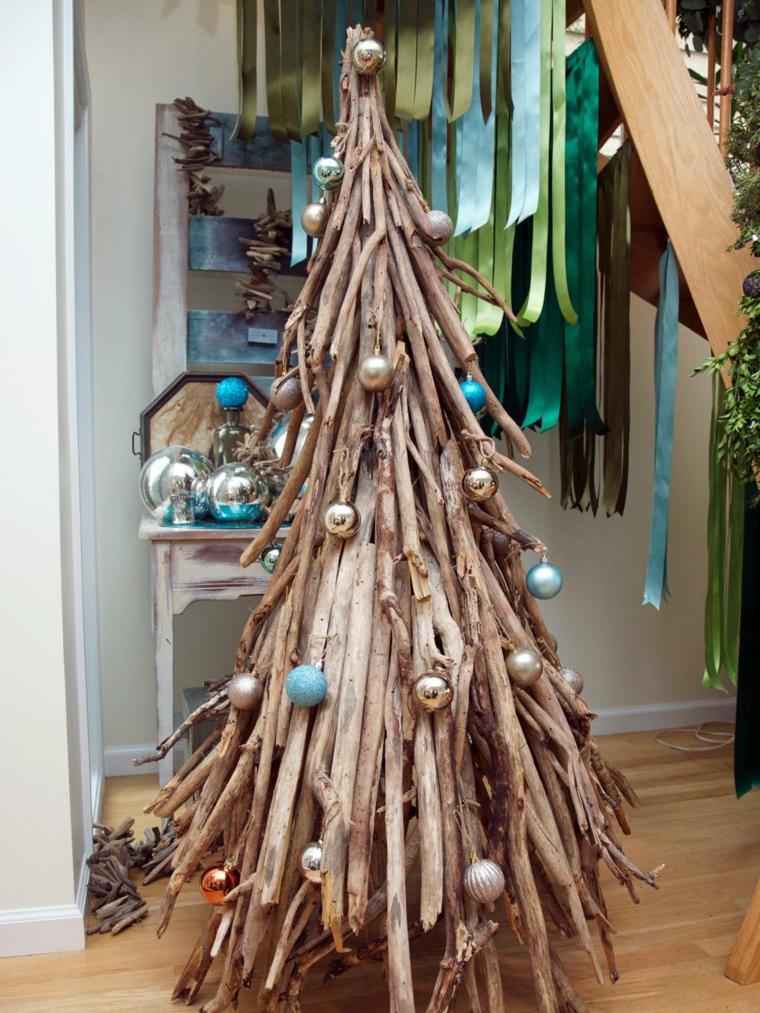 Decorazioni di Natale fai da te, legnetti di varia dimensioni a forma di albero e decorati con palline color oro e blu