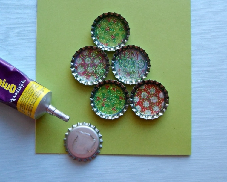 con i tappi delle bottiglie decorati a tema natalizio è possibile realizzare degli alberi per decorare i biglietti di auguri