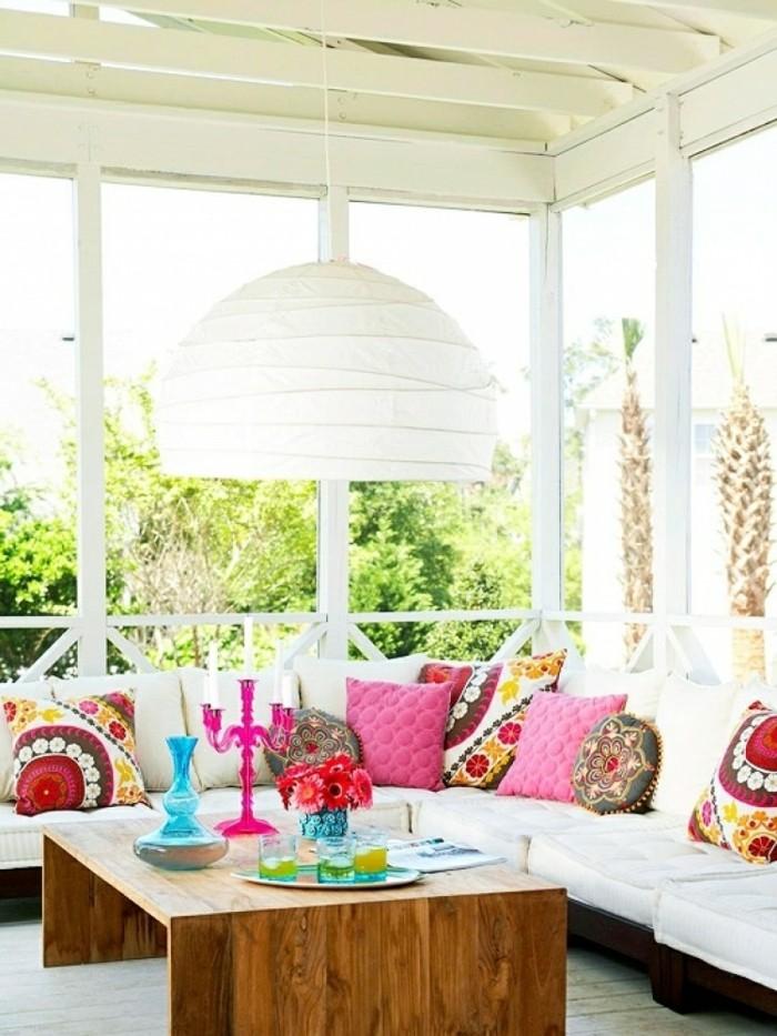 arredamento-terrazzo-coperto-pergolato-legno-colore-bianco-tavolino-basso-lampada-plafoniera-tanti-cuscini-colorati