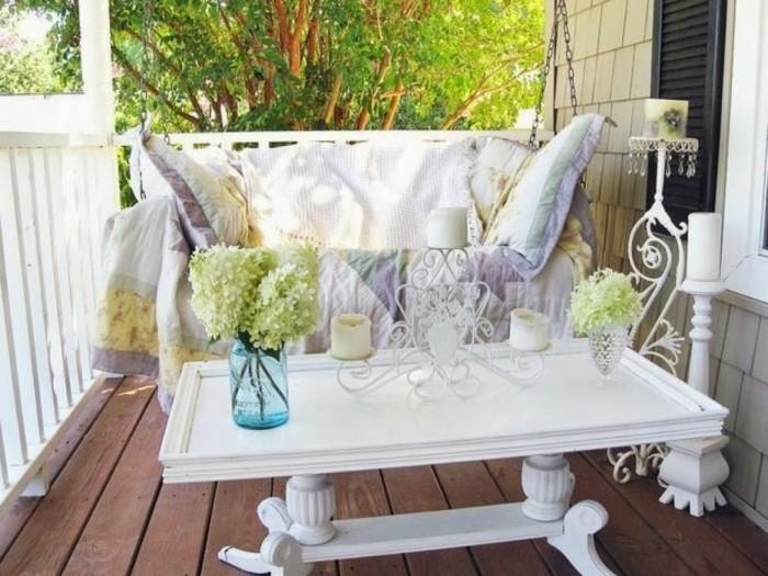 arredamento-terrazzo-pavimento-legno-tavolino-bianco-dondolo-cuscini-coperte-colorate