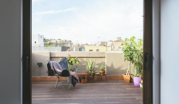 arredare-balcone-stile-minimal-piante-sedia-legno-coperta-pavimento-legno-ringhiera-cemento
