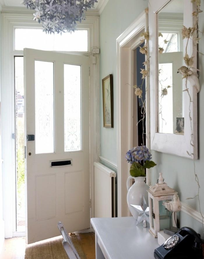 arredare-corridoio-stile-country-porta-di-ingresso-colore-bianco-tavolo-legno-specchio-vaso-fiori-lampadario