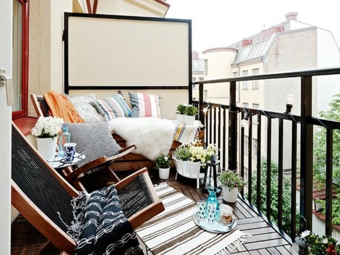 arredare-il-balcone-lampadine-righiera-ferro-battuto-sdraio-legno-panchina-tappeto-etnico-cuscini-coperte-piante-decorazioni