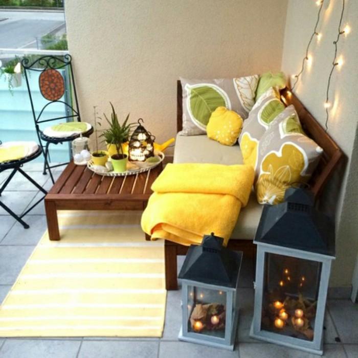 arredare-il-balcone-mobili-da-esterno-legno-cuscineria-grigio-giallo-sedie-pighevoli-ferro-decorazione-tappeto-lanterne-fili-luce