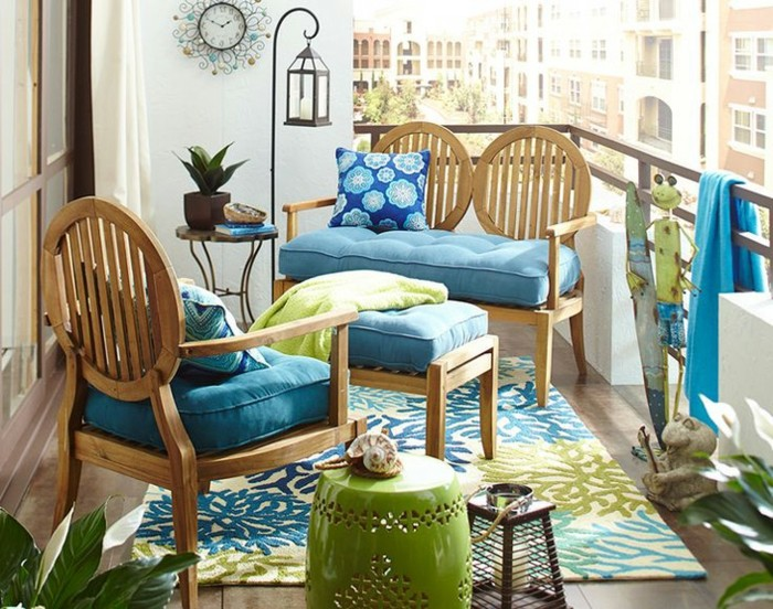 arredare-il-balcone-mobili-legno-eleganti-cuscini-colore-blu-tappeto-abbinato-ringhiera-ferro-battuto