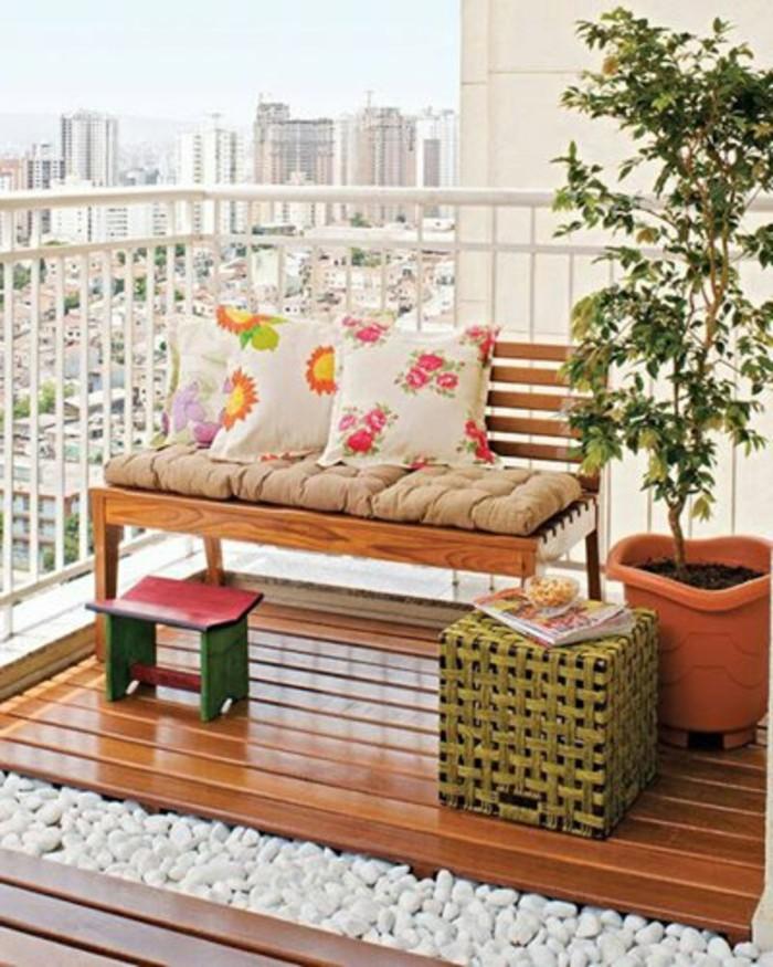 arredare-il-terrazzo-panchina-legno-pavimento-parquet-da-esterno-decorazione-sassi-piante-cuscineria