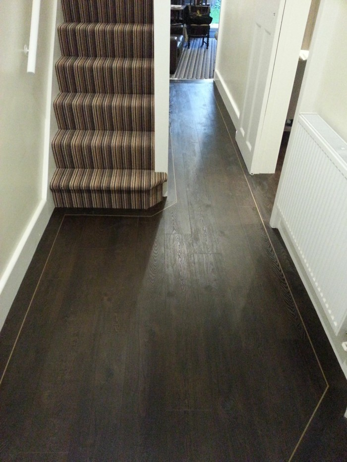 arredare-un-corridoio-pavimentazione-legno-colore-scuro-scale-tappeto-atnico-pareti-bianche