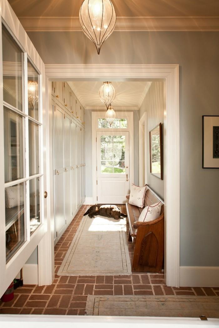 arredare-un-corridoio-tappeto-colore-chiaro-panchina-legno-lampade-da-soffitto-porta-di-ingresso-vetro-armadio-muro
