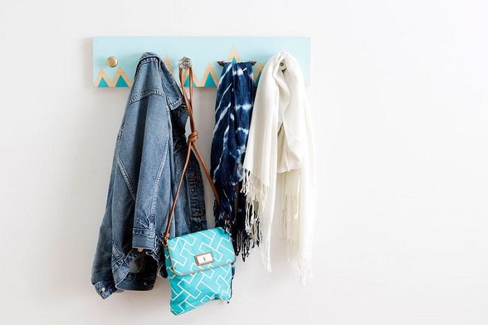 Fai da te creativo per allestire una parete bianca in corridoio, attaccapanni da parete in legno colorato di azzurro e color oro