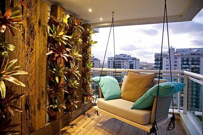balcone-piccolo-pavimento-legno-dondolo-cuscini-colorati-giardino-verticale-tante-piante-faretti-led-soffitto