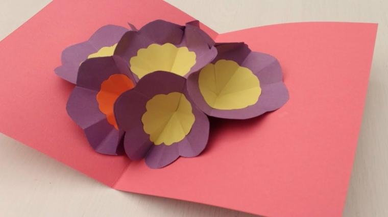 biglietto auguri natale, un cartoncino rosa decorato con dei fiori pop up incollati al centro