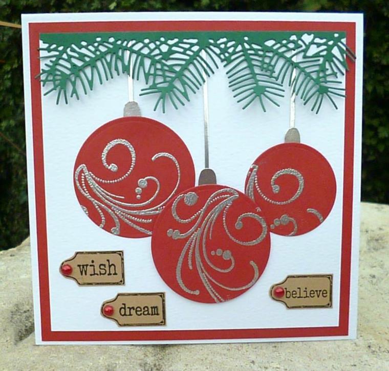 biglietti natale, un cartoncino bianco decorato con delle palline rosse e argento e delle scritte di auguri