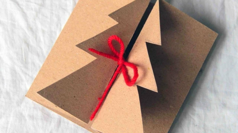 auguri natale, un cartoncino con al centro un albero di natale che si apre decorato con un fiocco