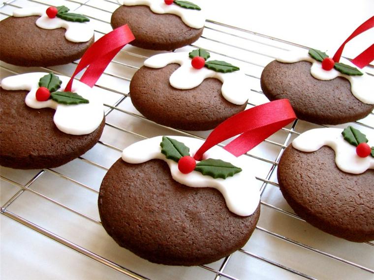Dolci natalizi, biscotti dalla forma rotonda al cacao con decorazione pasta di zucchero bianca e nastro rosso per appendere