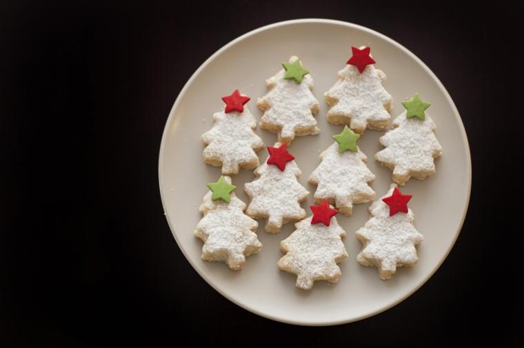 Biscotti semplici, forma alberelli di Natale con una spolverata di zucchero a velo e stelline in cima di pasta di zucchero