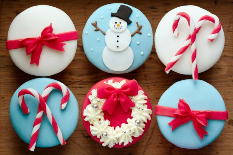 Decorare i biscotti di Natale con della pasta di zucchero colorata e formine di pupazzo di neve, fiocchi e bastoncini