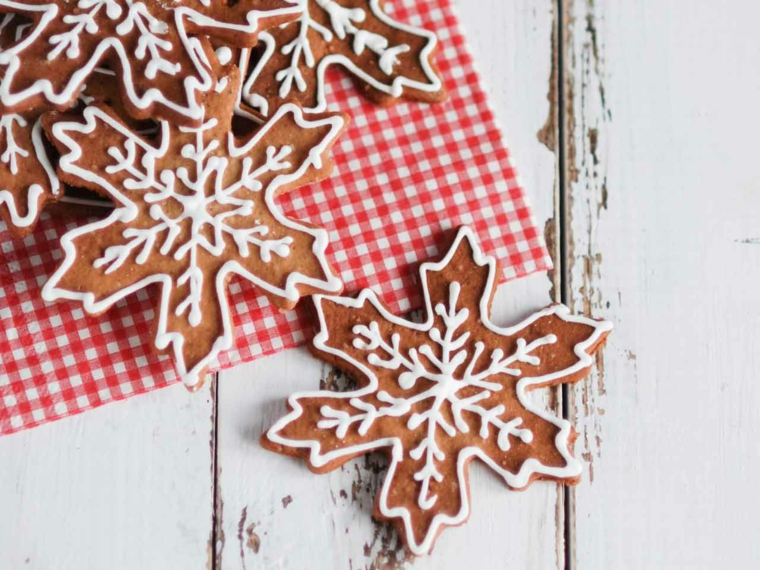 Dolci natalizi, biscotti dalla forma di fiocchi di neve decorati con della glassa reale di colore bianco