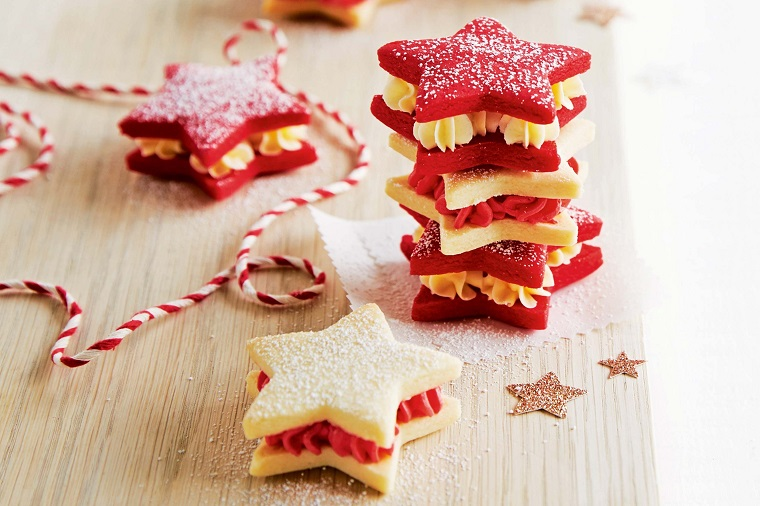 Dolci natalizi, biscotti a forma di stella di diverso colore a sandwich e mousse dolce tra di loro
