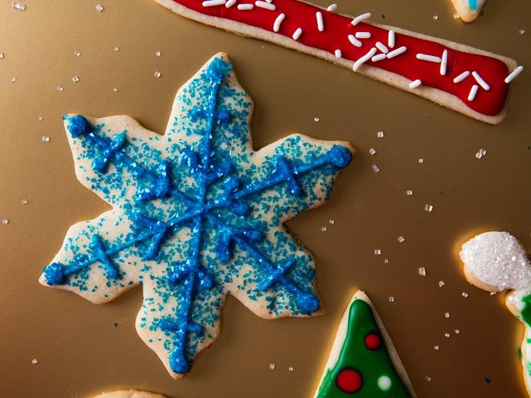 Ricette di Natale, biscotto forma fiocco di neve e decorato con del glitter azzurro commestibile per dolci
