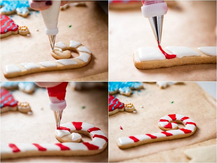 Dolci natalizi, come decorare con la glassa reale un biscotto con la forma a bastoncino natalizio